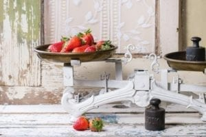 Weights and vintage scales with fresh strawberries over white wooden table