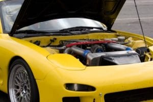 A closeup of a modern sports car with the hood popped open.